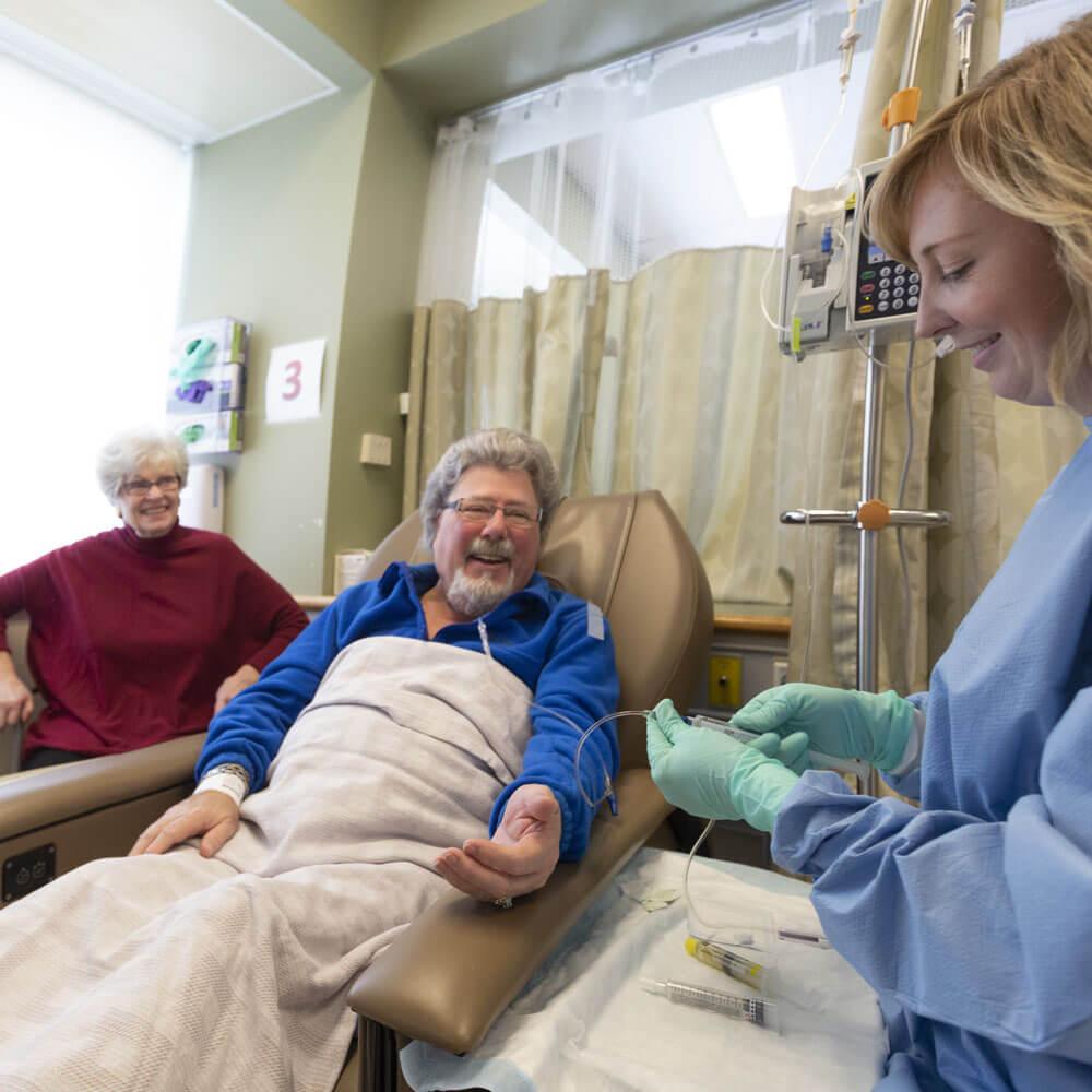 Cancer care nurse preparing IV for happy senior patient