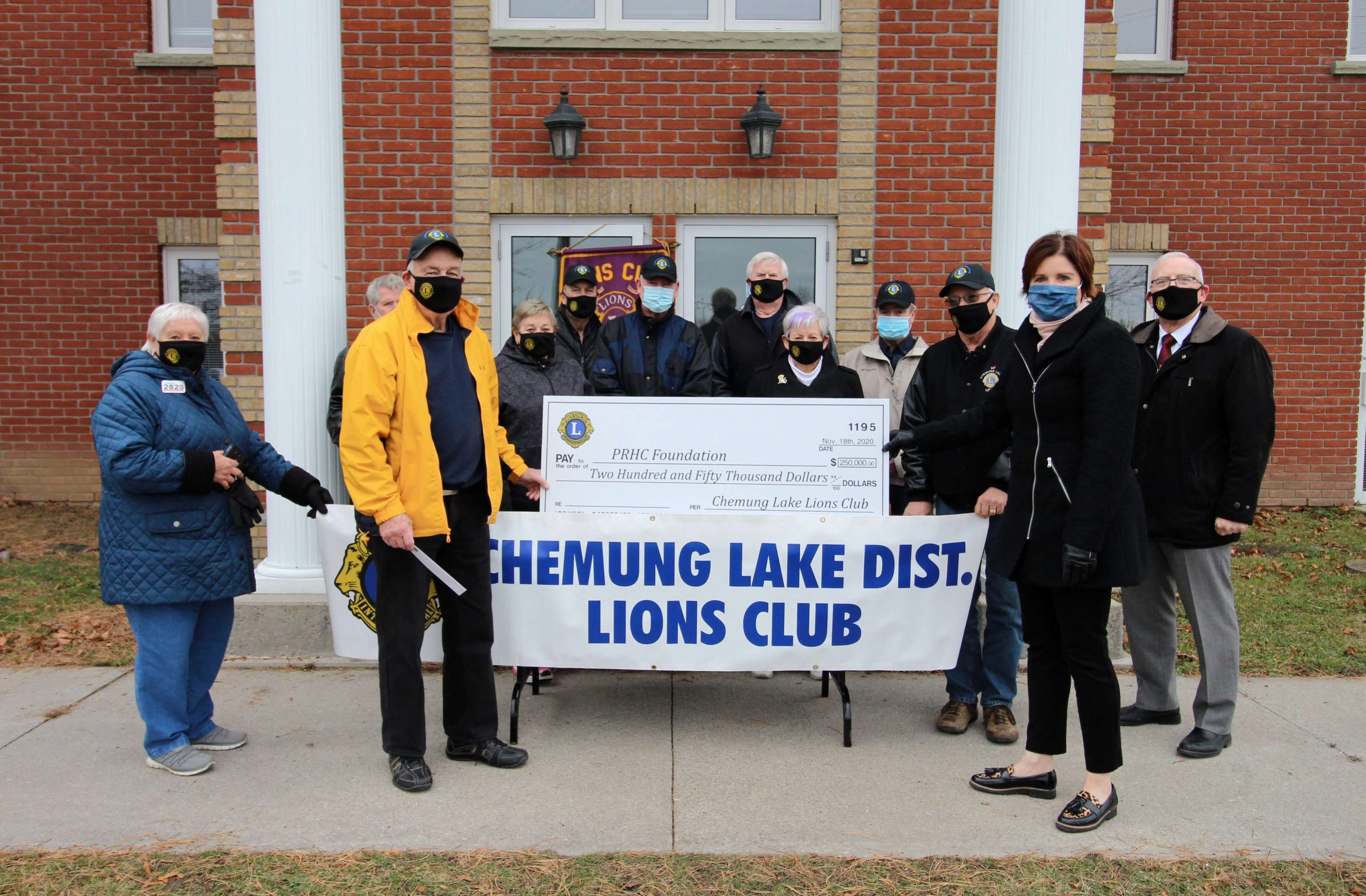 Lions Club member presents a large cheque