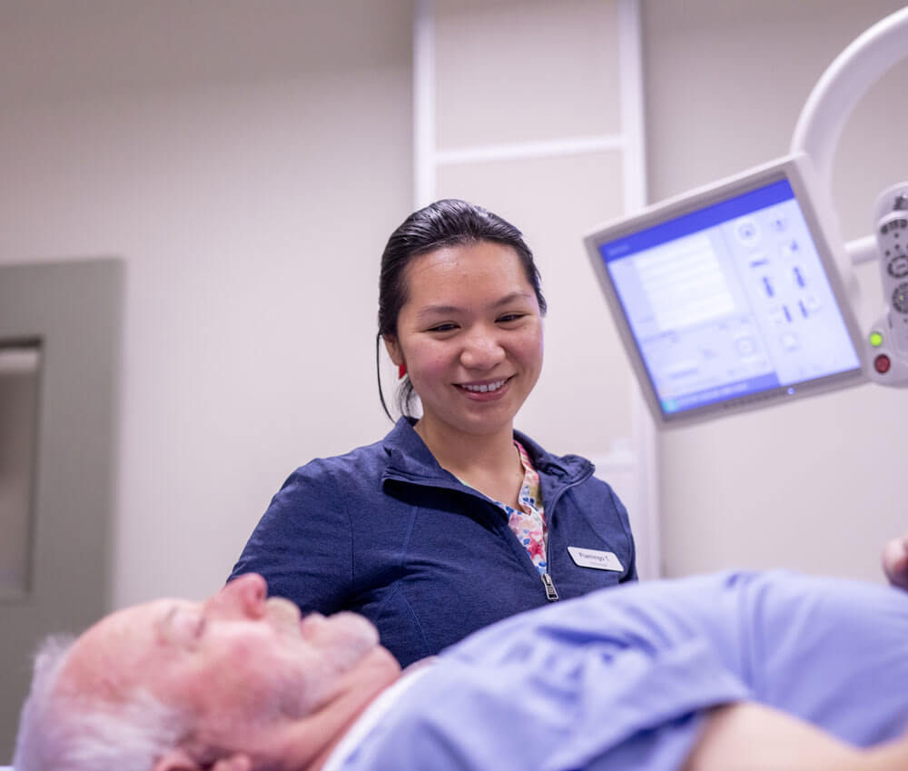 Smiling technologist preparing patient for SPECT/CT scan