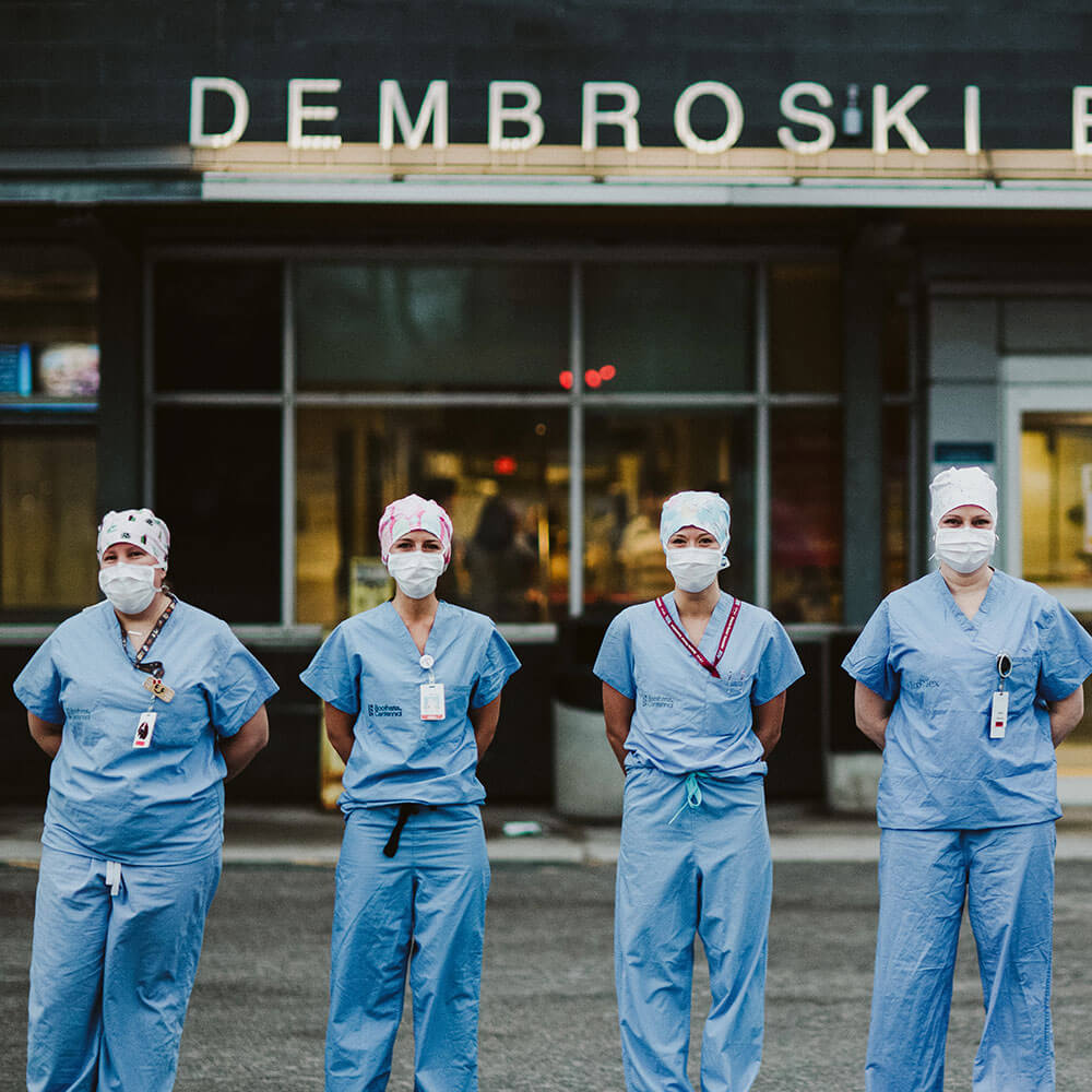 Nurses dressed in masks and scrubs standing outside the Emergency room entrance