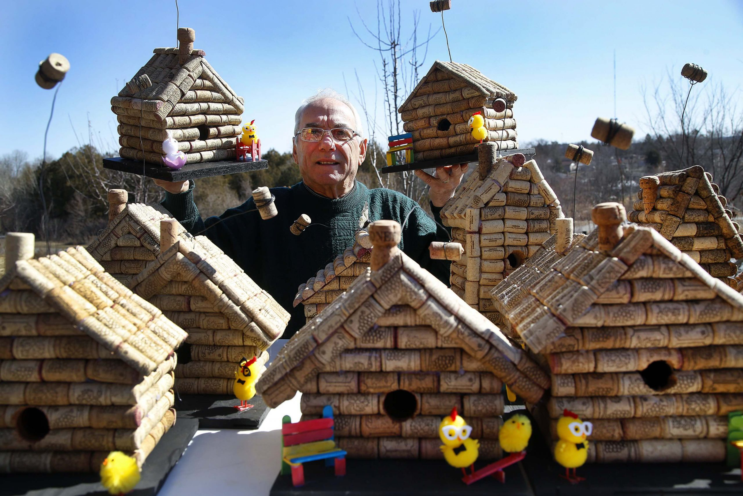 A man stands behind a table of birdhouses holding two birdhouses in the air