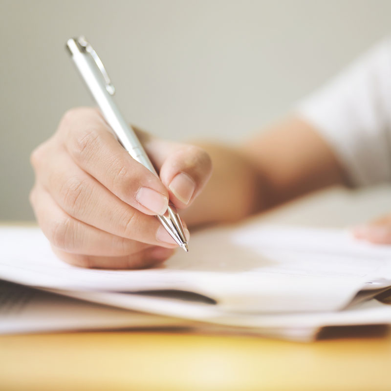 Hand signing papers with pen