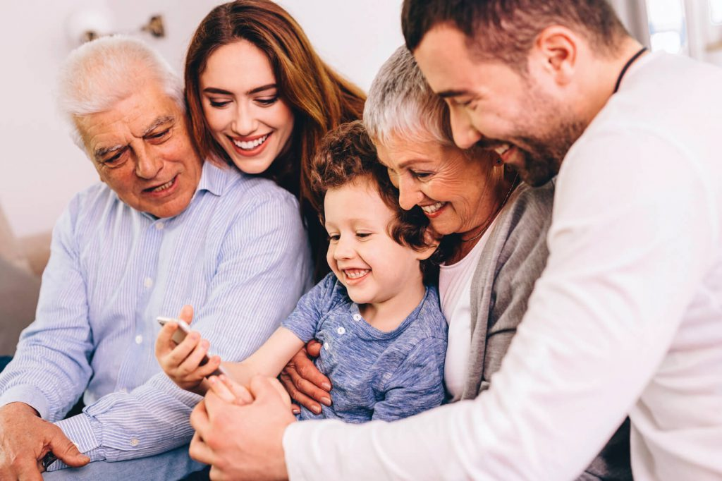 Child closely embraced by parents and grandparents