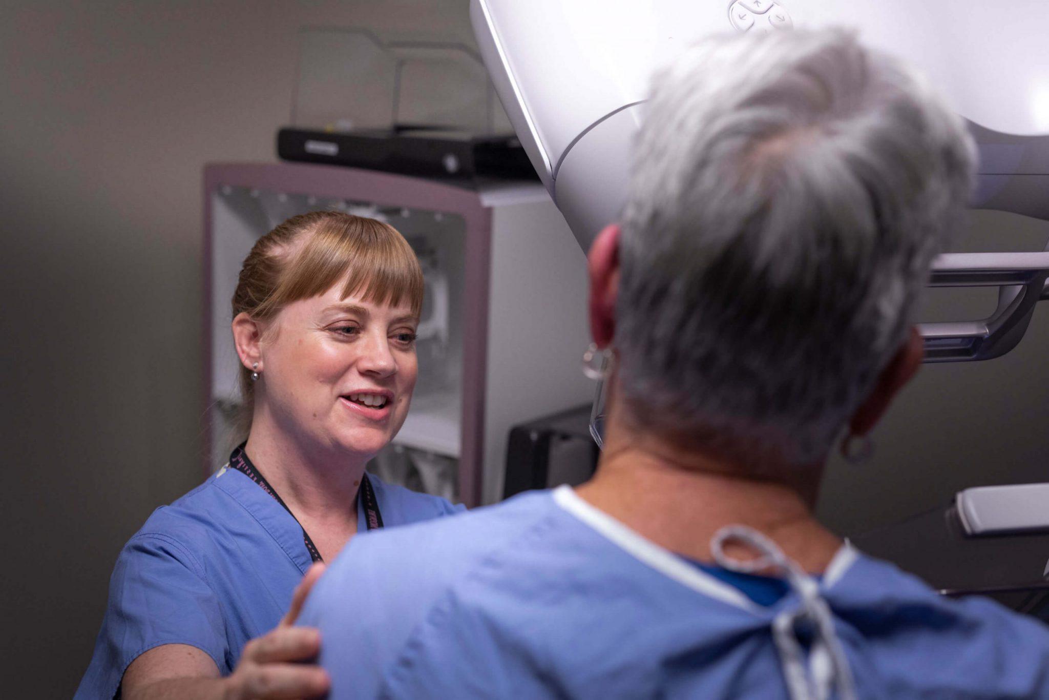 Nurse supporting patient through mammogram screening