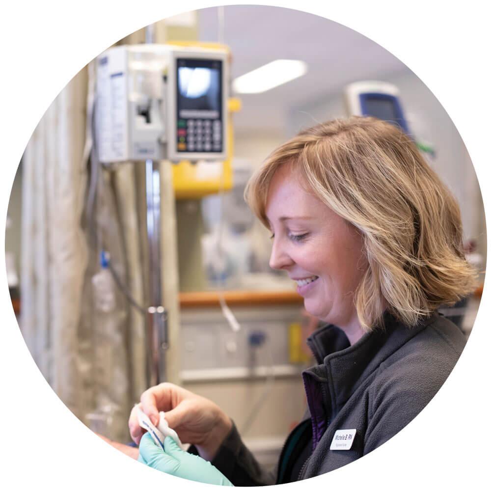 Happy nurse preparing needle for chemo therapy treatment