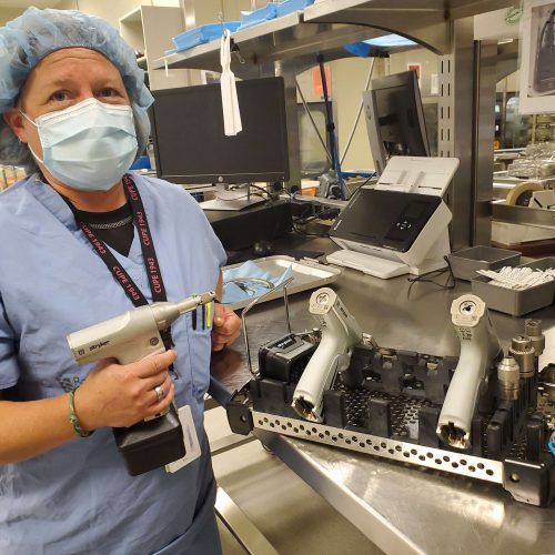 Masked surgical suite assistant holds a surgical tool