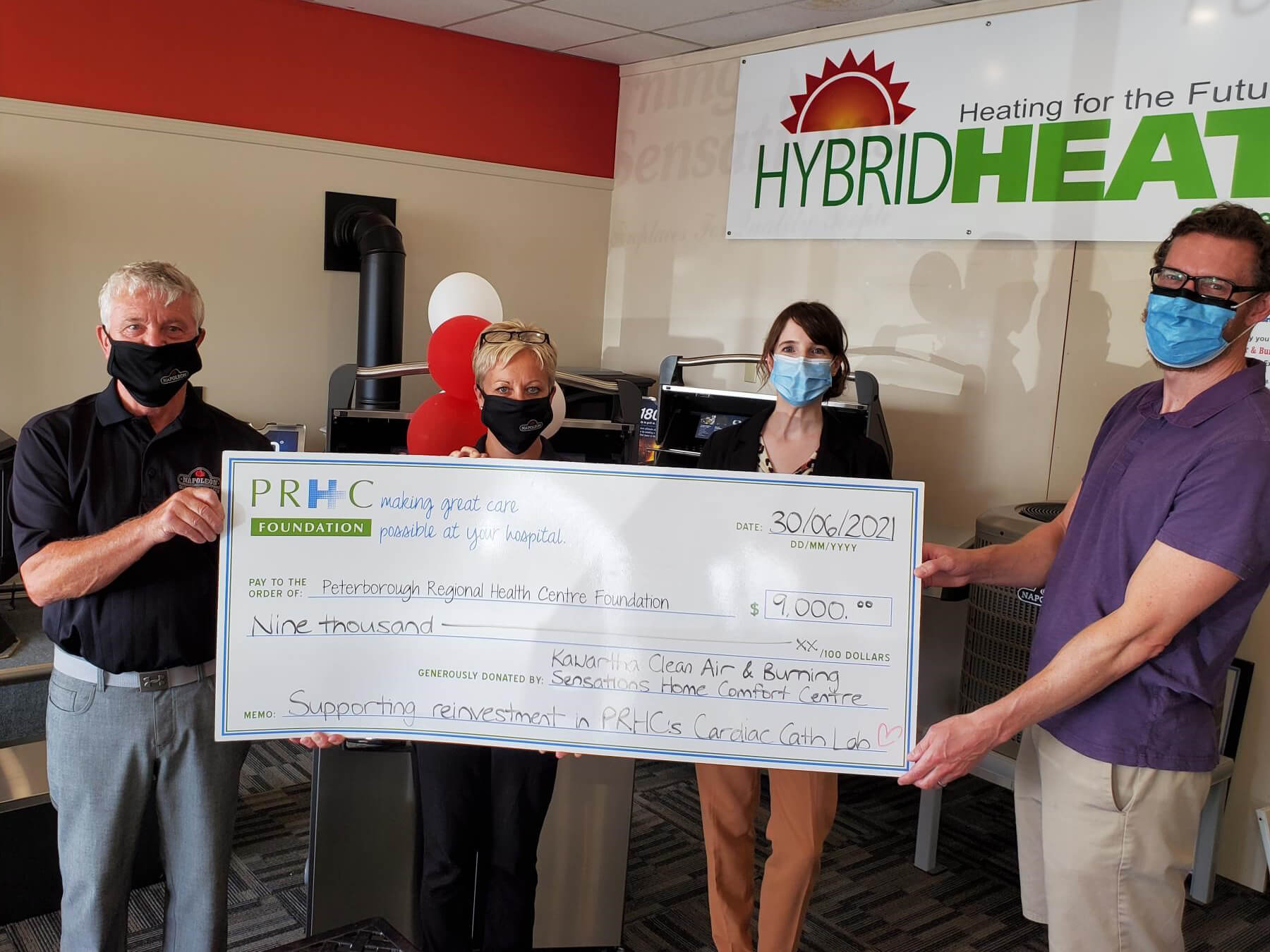 Four people wearing masks hold an oversized donation cheque for $9,000